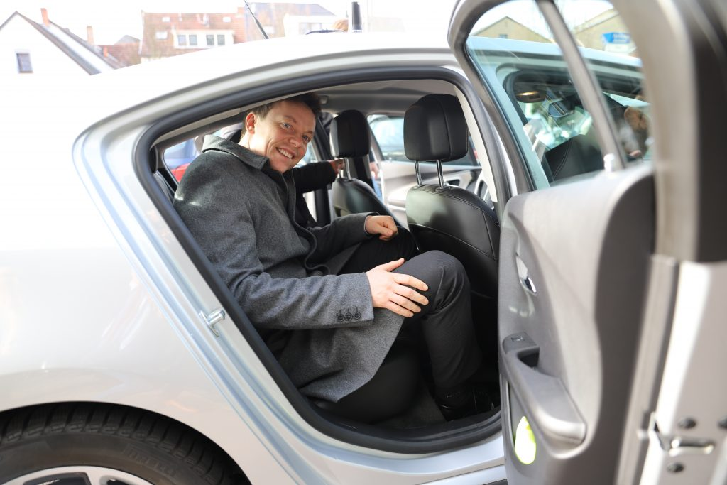 Prime Minister Tobias Hans in the back of a tets vehicle.