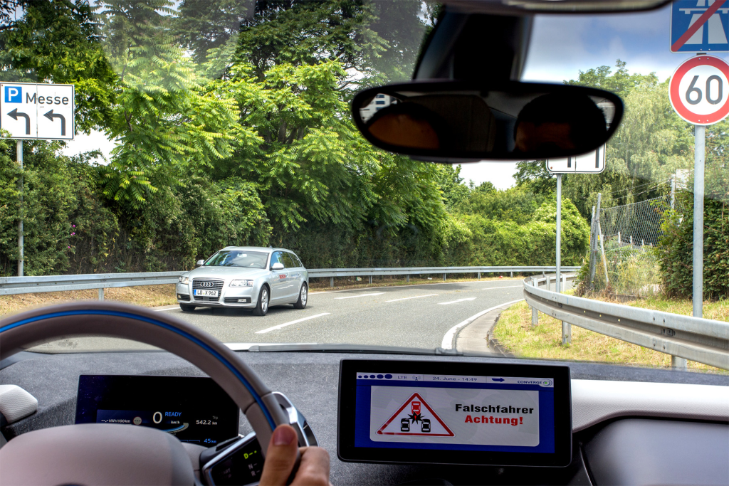 A wrong-way-driver-message is show to the driver in a vehicle. A car driving in the wrong direction is seen in the front.